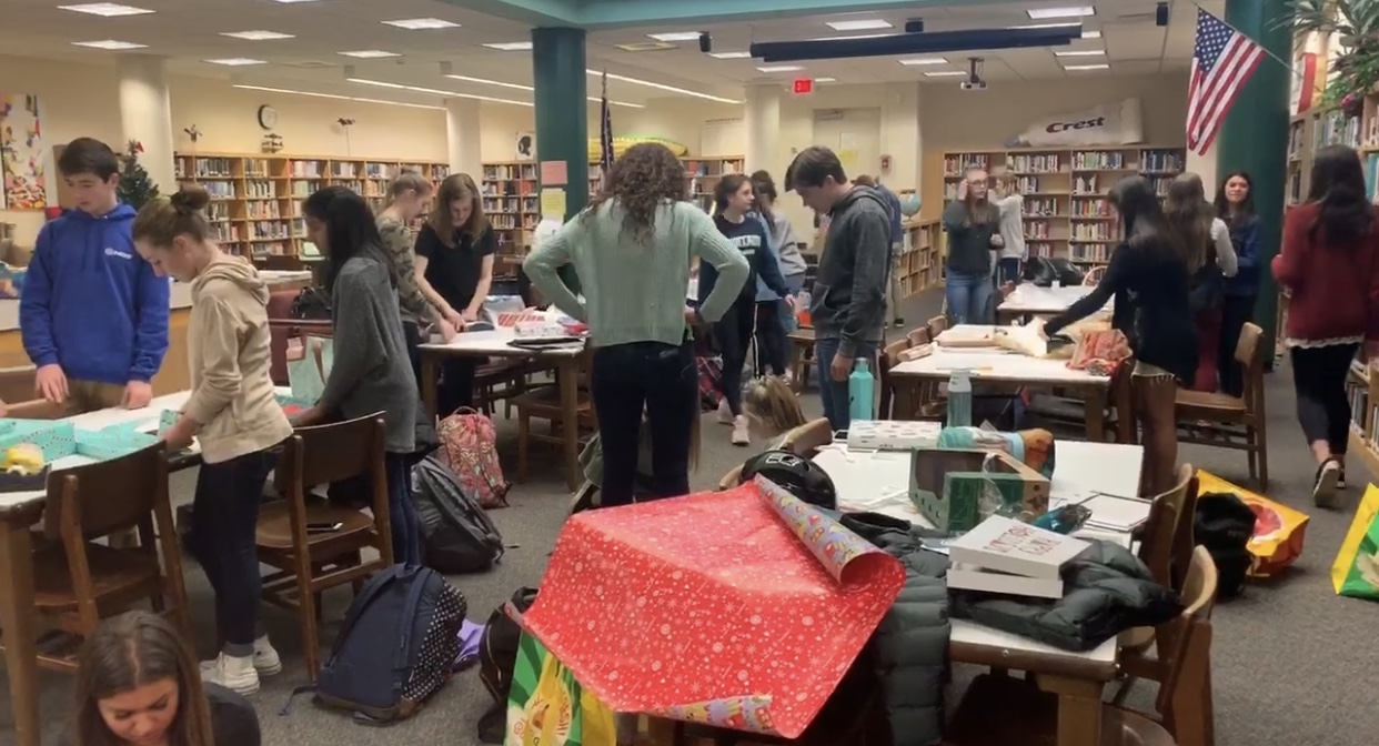 Student government wrapping presents for adopt-a-families.