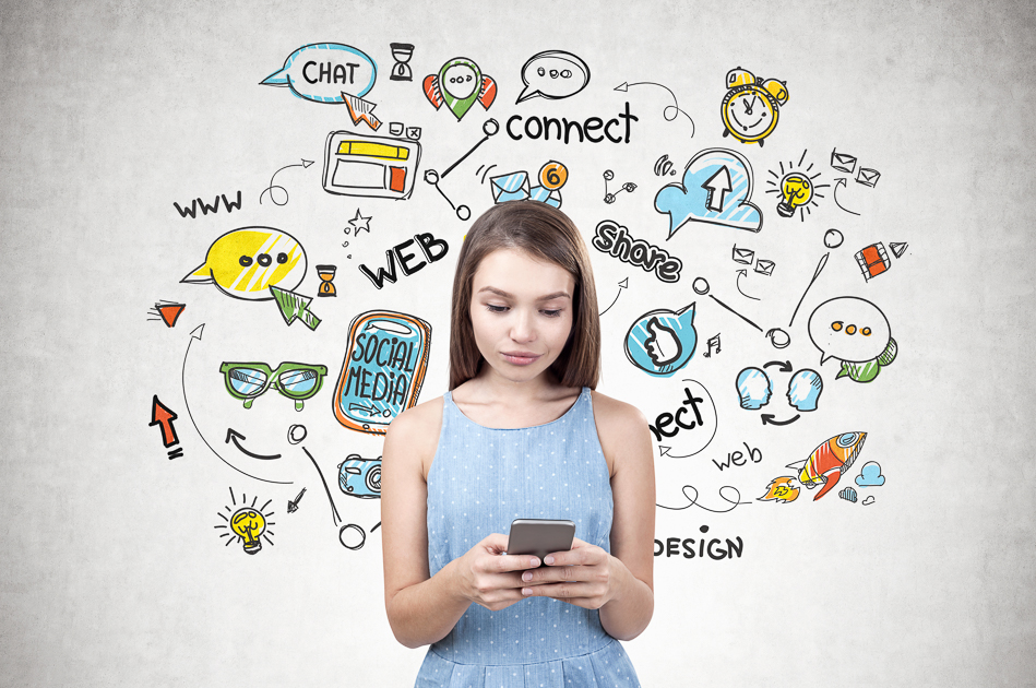 Young woman with long fair hair wearing blue dress holding smartphone with both hands and looking at the screen. Concrete wall with colorful social media icons
