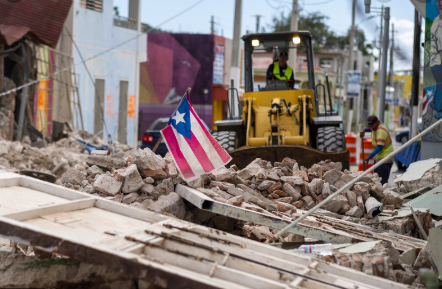 A Puerto Rican flag waves on top of a pile of rubble as debris is removed from a main road in Guánica. Ricardo Arduengo /AFP via Getty Images