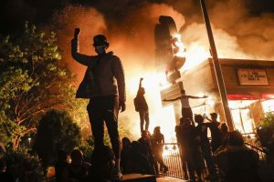 Protesters standing beside a burning restaurant.